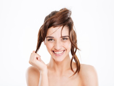 Beauty portrait of cheerful young woman touching hair and having fun over white background