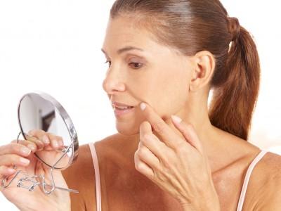 Ältere Frau untersucht ihre Falten am Mundwinkel im Handspiegel