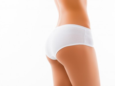 Close up photo of shapely woman's back in white panties