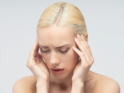 Headache concept. Young attractive blonde woman touching her head isolated on white background.