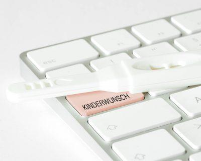 Ein Schwangerschaftstest und eine Computertastatur mit der Taste