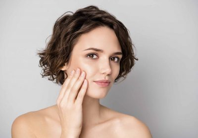 Portrait of lovely pretty charming girl have skin care plastic surgery, procedure look in mirror touch finger hands face isolated over gray color background